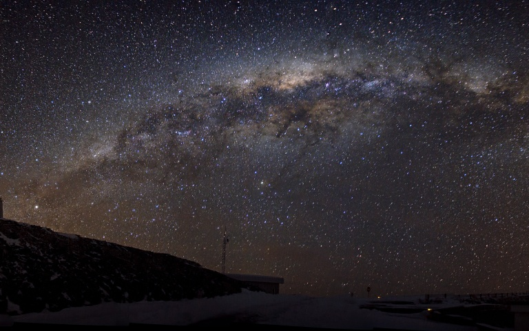 "This panoramic photograph, taken by Alexandre Santerne, shows an insider's view of the disc of the Milky Way, our home galaxy, as well as a cold winter's night, with a sprinkling of snow at ESO's La Silla Observatory in Chile. From our vantage point within it, the disc of the Milky Way appears as a sparkling ribbon of stars stretching across the sky. In this panorama, the Milky Way is distorted into an arc by the wide-angle projection. Peeking over the hill on the left of this photo is the ESO 3.6-metre telescope, home to the world's foremost exoplanet hunter, HARPS (the High Accuracy Radial velocity Planet Searcher). On the far right is the Swiss 1.2-metre Leonhard Euler Telescope, built and operated by the Geneva Observatory. There are a number of reasons why La Silla is such an ideal location for observing the night sky in general, and the Milky Way in particular. Firstly, it's located in the southern hemisphere, giving us a better view of the richer central region of the galaxy, and secondly, it's located far from light and urban pollution, at an altitude of 2400 metres above sea level, making the nights dark and the atmosphere clear. Alexandre submitted this photograph to the Your ESO Pictures Flickr group. The Flickr group is regularly reviewed and the best photos are selected to be featured in our popular Picture of the Week series, or in our gallery. Since submitting the photo, Alexandre has also become an ESO Photo Ambassador. Links This photograph, with annotations, on Alexandre Santerne's Flickr photostream Alexandre Santerne's Flickr photostream The ""Your ESO Pictures"" Flickr group The ""Your ESO Pictures"" announcement ESO Photo Ambassadors"
